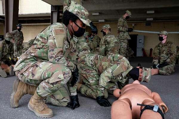 Air Force trainee Beauxerykah Betterson helps her fellow flight member Savannah Houston practice first aid drills during BEAST week.