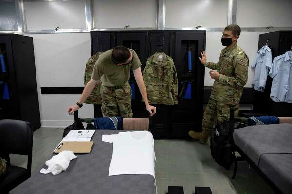 Dorm chief Dominic Hadrick gives a fellow trainee advice on how to correctly fold his shirt. The pandemic forced changes to Air Force basic training, including fewer recruits per dormitory at Joint Base San Antonio-Lackland.