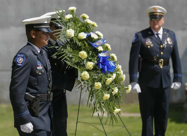 Members of the Conroe Police Department present a ceremonial wreath in honor of Sgt. Ed Holcomb, Jr. during the annual police memorial at Heritage Park, Thursday, May 13, 2021, in Conroe. The event, which was held virtually last year, honors the Conroe police officer and others who have died in the line of duty as part of National Police Week. Photo: Jason Fochtman/Staff Photographer / 2021 © Houston Chronicle