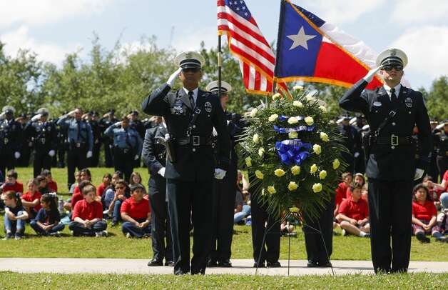 Police officers and other law enforcement salute as Taps is played during the annual police memorial in honor of Sgt. Ed Holcomb, Jr. at Heritage Park, Thursday, May 13, 2021, in Conroe. The event, which was held virtually last year, honors Holcomb and other officers who have died in the line of duty as part of National Police Week. Photo: Jason Fochtman/Staff Photographer / 2021 © Houston Chronicle