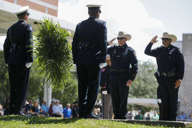 Magnolia Police officers salute a ceremonial wreath in honor of Sgt. Ed Holcomb, Jr. during the annual police memorial at Heritage Park, Thursday, May 13, 2021, in Conroe. The event, which was held virtually last year, honors the Conroe police officer and others who have died in the line of duty as part of National Police Week. Photo: Jason Fochtman/Staff Photographer / 2021 © Houston Chronicle