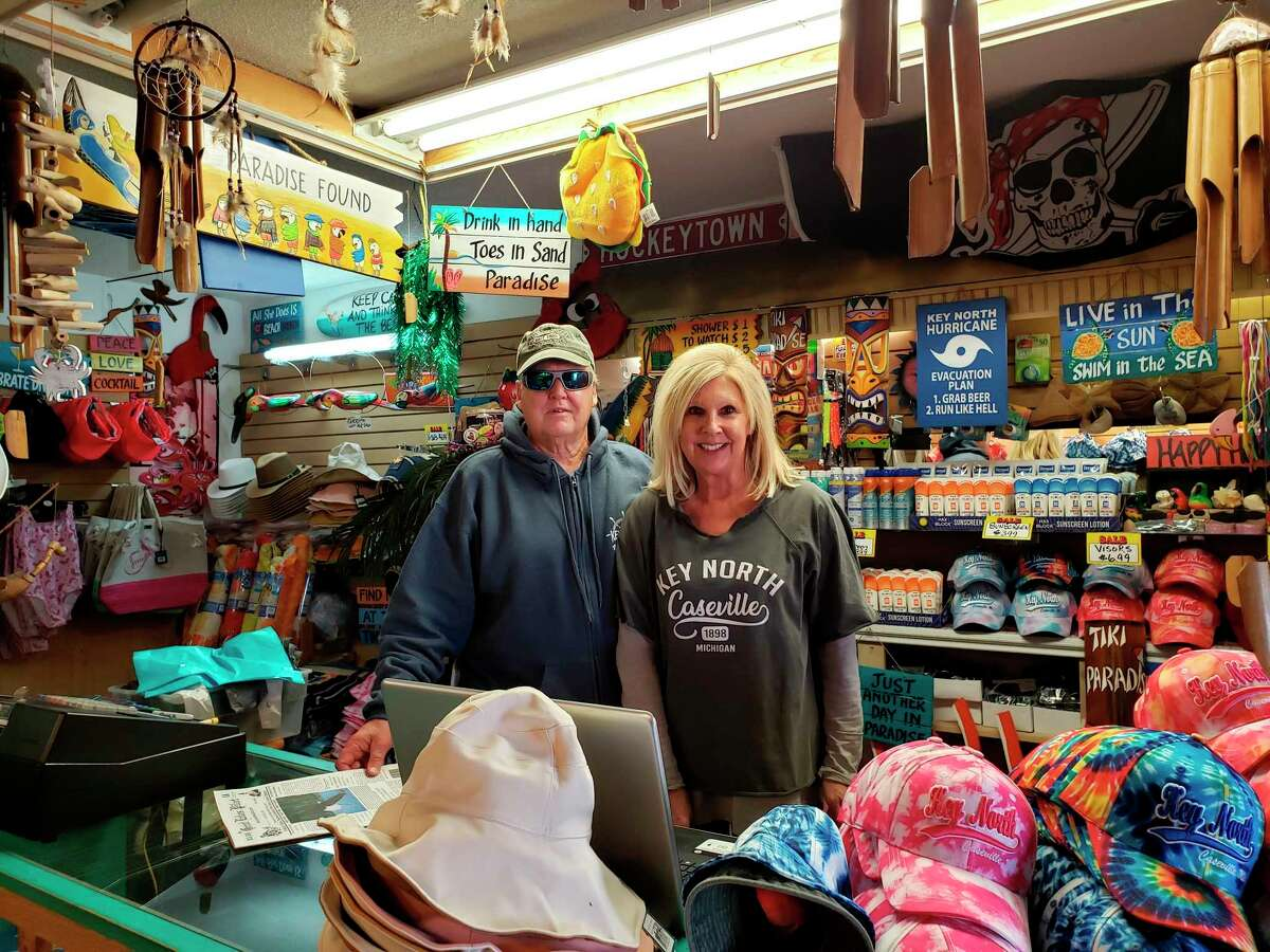 Rob and Linda Pillsworth pose for a photo at the front counter of Key North Surf Shop in Caseville. The two have operated the establishment since the mid-90s. (Robert Creenan/Huron Daily Tribune)