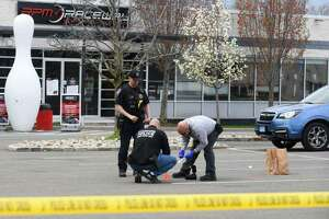 Investigators survey the scene of a fatal shooting in the parking lot of RPM Raceway in Stamford, Conn., on Monday, April 19, 2021. The fatal shooting occurred the night before.