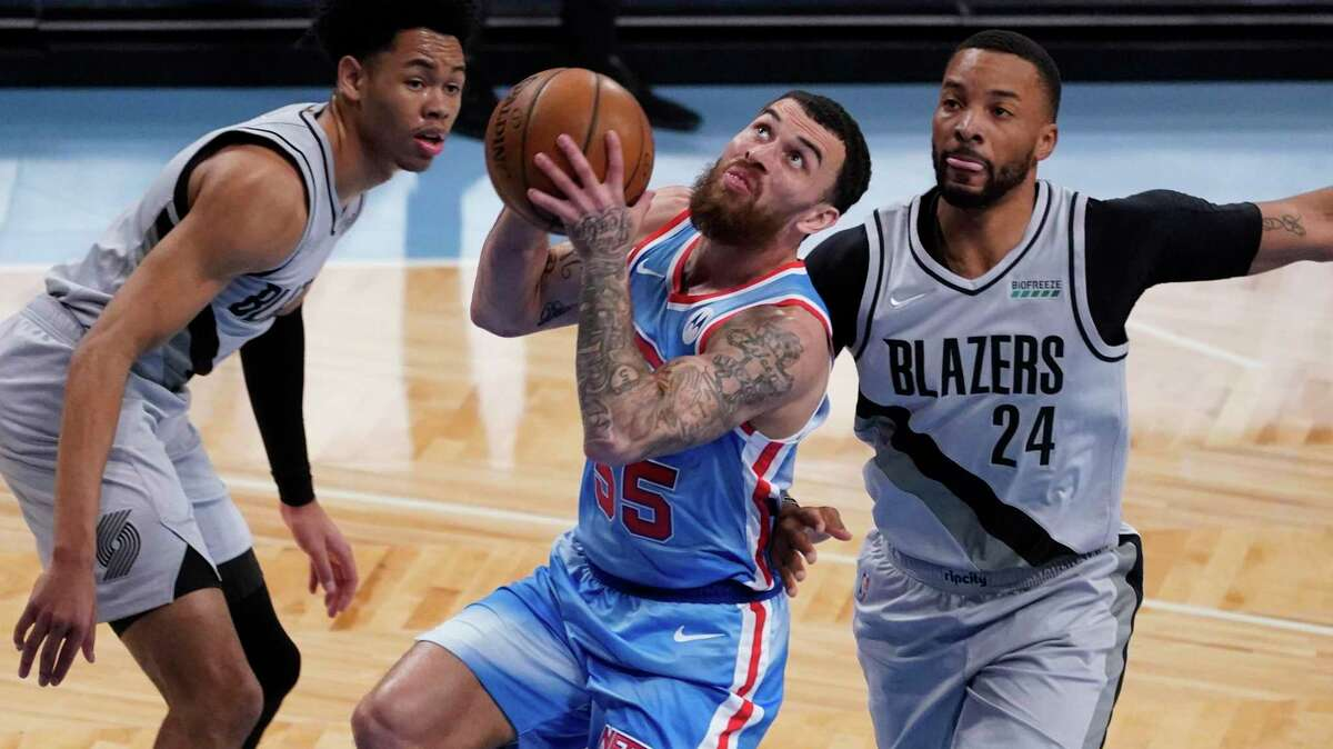 Brooklyn Nets guard Mike James (55) drives to the basket against Portland Trail Blazers forward Norman Powell (24) and guard Anfernee Simons during the first half of an NBA basketball game, Friday, April 30, 2021, in New York. (AP Photo/Mary Altaffer)