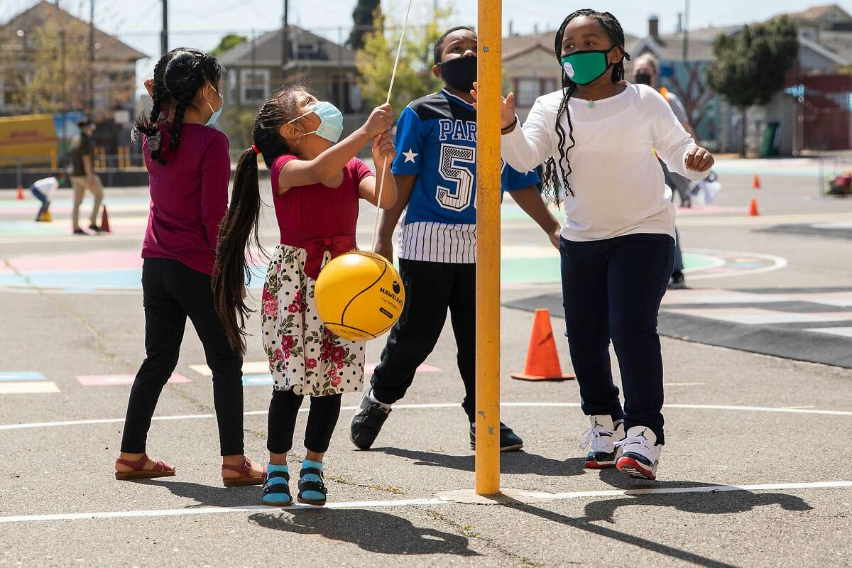 Second grade students wear masks while playing during recess at Garfield Elementary School in Oakland, on April 19, 2021.