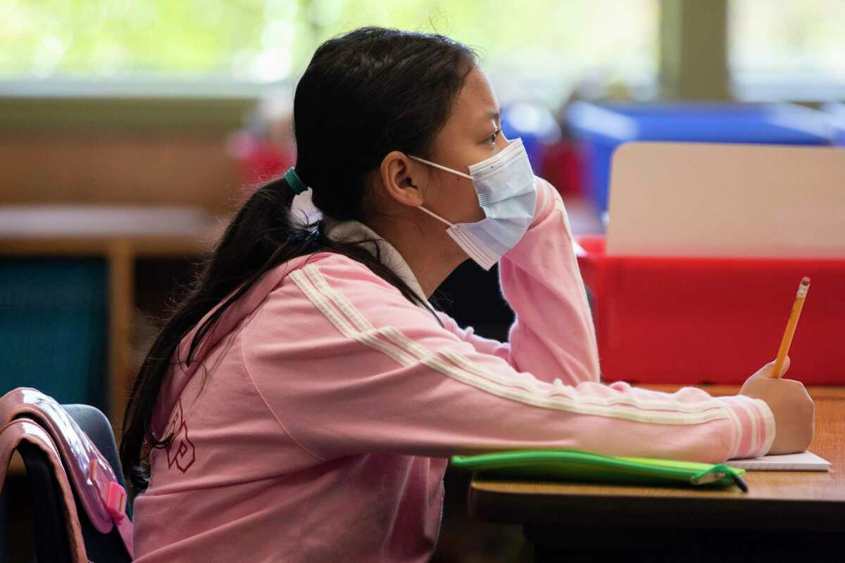 Fourth grade students wear masks while working on schoolwork at Garfield Elementary School in Oakland, Calif. Monday, April 19, 2021 during the first day of partial school-wide, in-person learning.