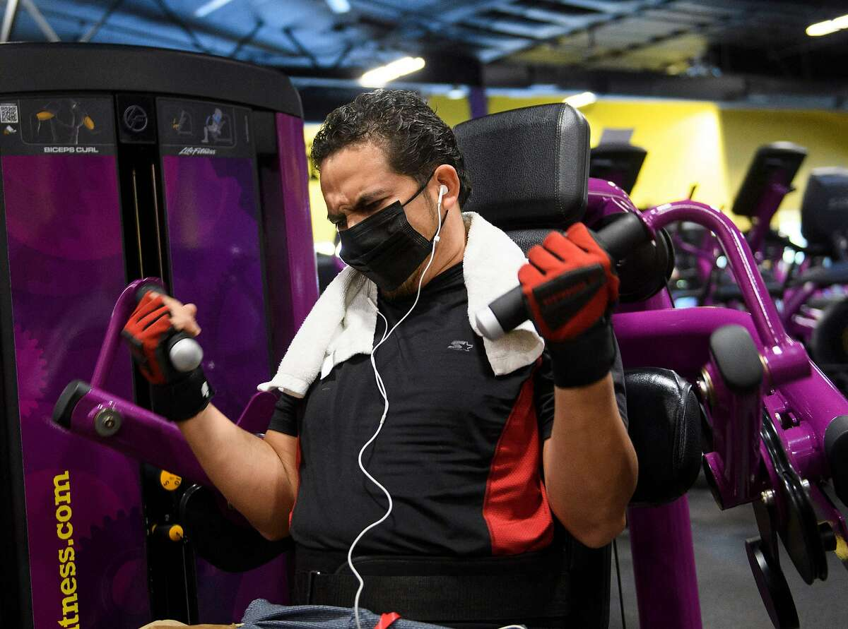 (FILES) In this file photo taken on March 16, 2021, a customer wears a face mask inside a Planet Fitness Inc. gym as the location reopens after being closed due to the Covid-19 pandemic in Inglewood, California. - Covid cases are declining quickly while vaccinations continue to rise slowly but surely in the US, the former epicenter of the pandemic. Many experts believe the time will soon be right for the federal government to ease its recommendations on indoor masking across the board, and say doing so could help encourage more vaccine holdouts about the clear benefits of getting their shots. (Photo by Patrick T. FALLON / AFP) (Photo by PATRICK T. FALLON/AFP via Getty Images)