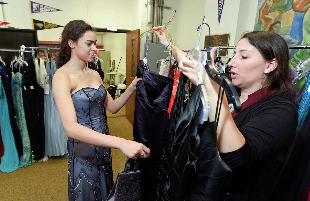 Claudia Moses, a senior at Stamford High School looks at various prom dresses with the help of teacher Mary Peters during the sixth annual Cinderella Project at Stamford High School on March 28, 2019.