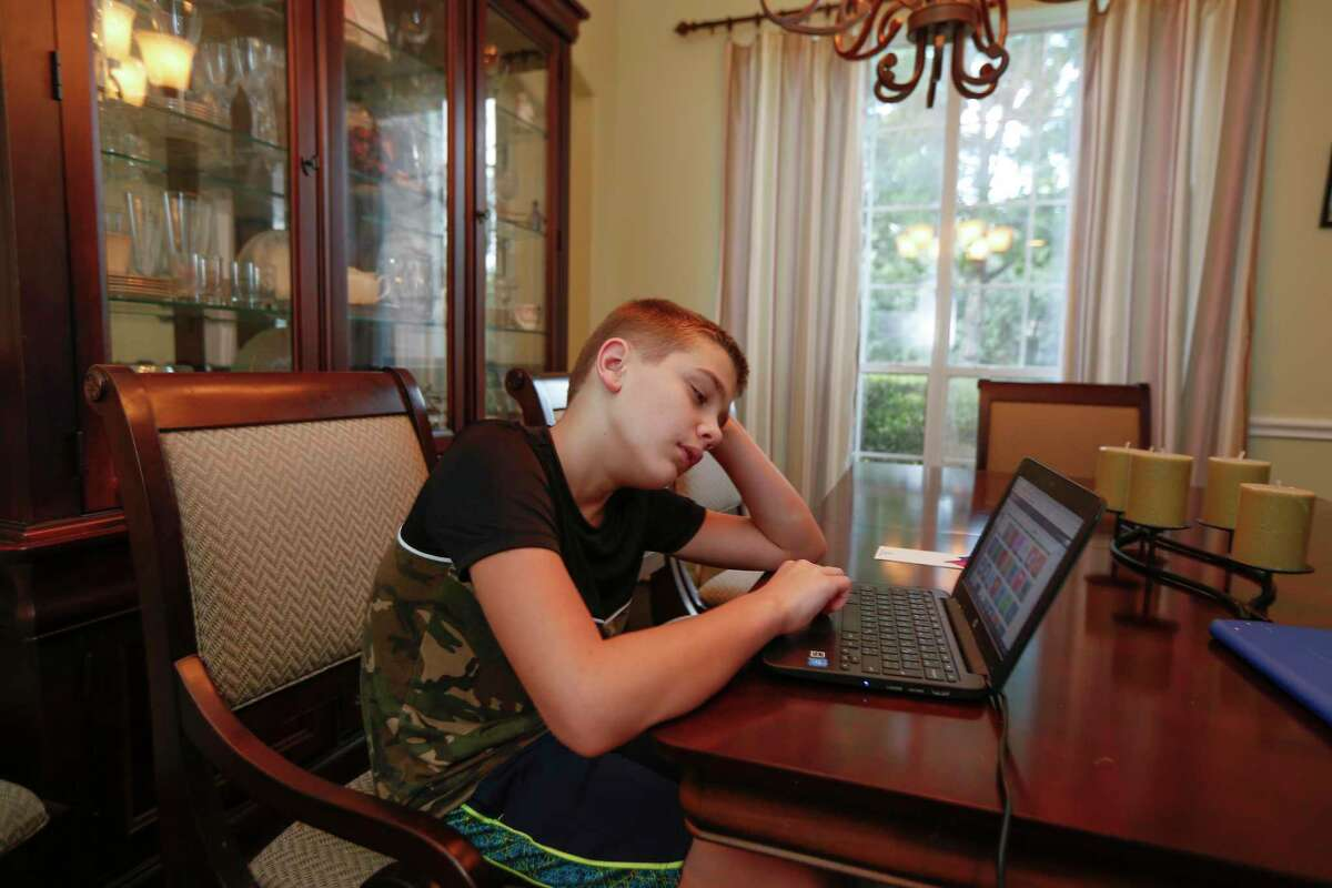 Seventh-grader Joseph Stidham seemed frustrated that his online assignments were not loaded when he checked in for school Monday, Aug. 24, 2020, in Humble.