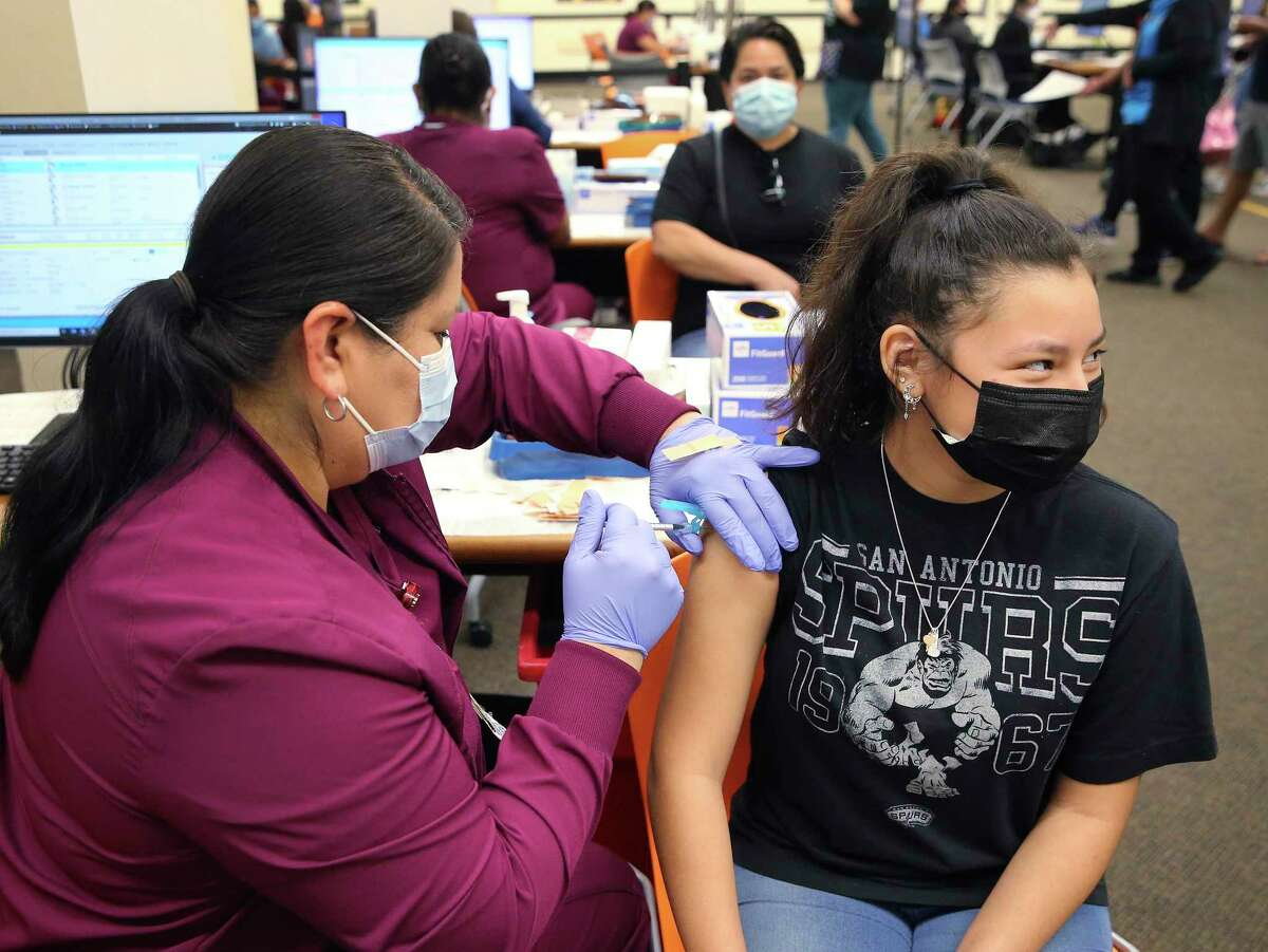 Aaliyah Aleman, 15, receives a Pfizer Covid-19 vaccine from Medical Assistant Yolanda Haro on Thursday, May 13, 2021. University Health is now vaccinating individuals who are 12 to 15-years old with the Pfizer COVID-19 vaccine, in addition to other older individuals. The shots are available on the upper level of the Wonderland of the Americas vaccine center, Monday through Friday. Vaccinations for those as young as 12 years follows authorization by the FDA, CDC and the State of Texas. Parents or guardians must provide proof of age and accompany those who are 12 to 17-years old.