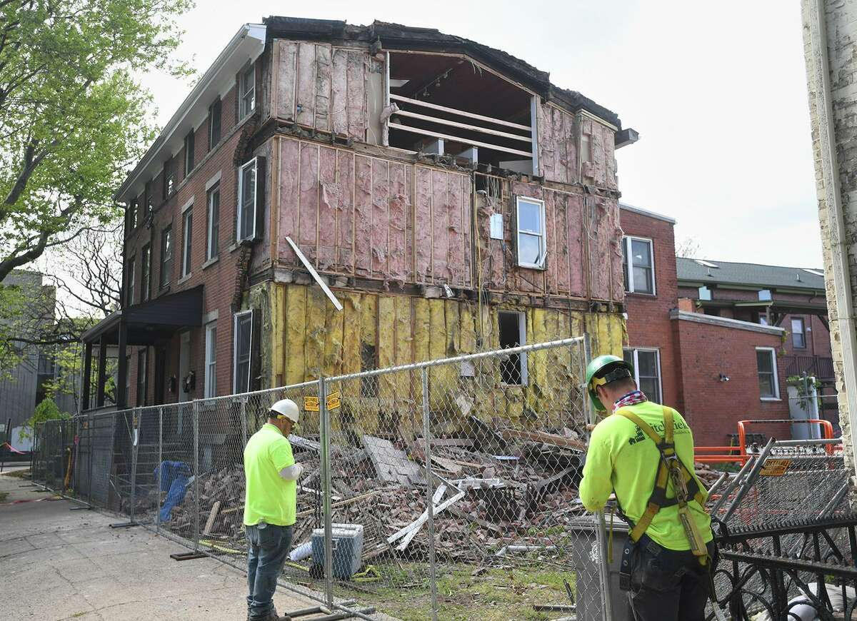 Workers put up temporary fencing outside a partial house collapse at 335 St. John St. in New Haven May 13, 2021.