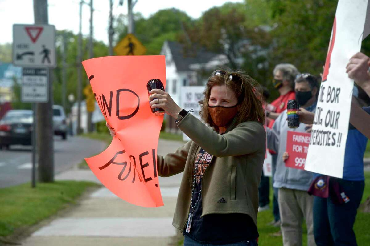 Sharon Young holds a sign while protesting on the lawn in front of Fairfield Hall, on the Western Connecticut State University midtown campus, Thursday afternoon. Young, a WCSU Social Work professor joined faculty member, some in red shirts representing their union CSU-AAUP, in protesting the Board of Regents' contract proposals. May 13, 2021, in Danbury, Conn.