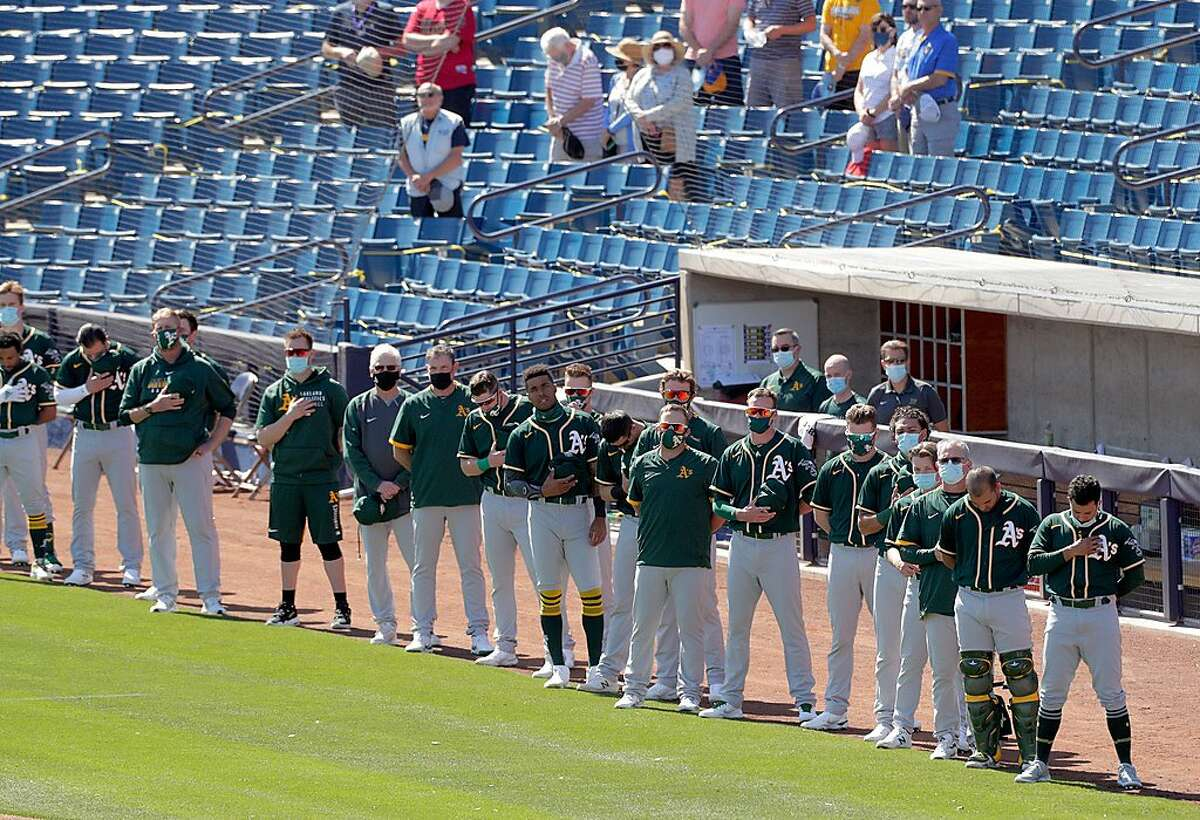 The players stand on the foul line during the national anthem before the Oakland Athletics played the American Family Field in Phoenix, Ariz., on Tuesday, March 2, 2021.
