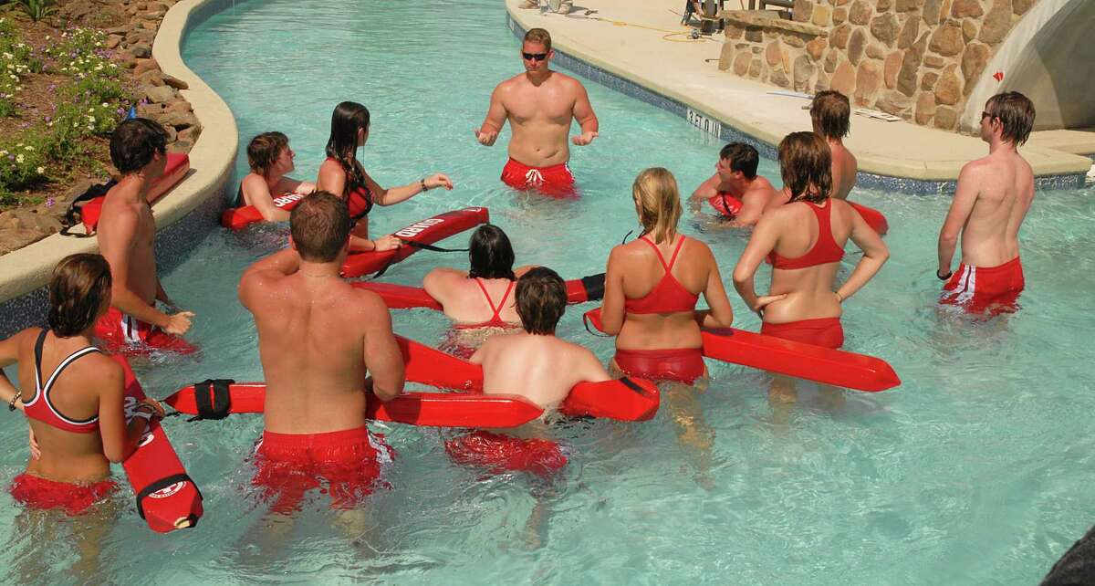 According to statistics provided by The Woodlands, the township hires between 330 and 350 lifeguards per year. In this archive image, Woodlands lifeguard instructor Stephen Hill talks to his lifeguards in the lazy river feature at the Rob Fleming Aquatic Center in The Woodlands' Creekside Park.