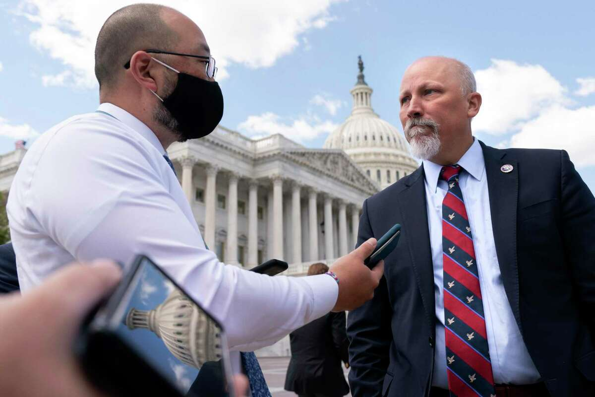 With the Capitol dome reflected in a cell phone, Rep. Chip Roy, R-Texas, right, speaks with reporters after a news conference, Wednesday, May 12, 2021, on Capitol Hill in Washington. (AP Photo/Jacquelyn Martin)