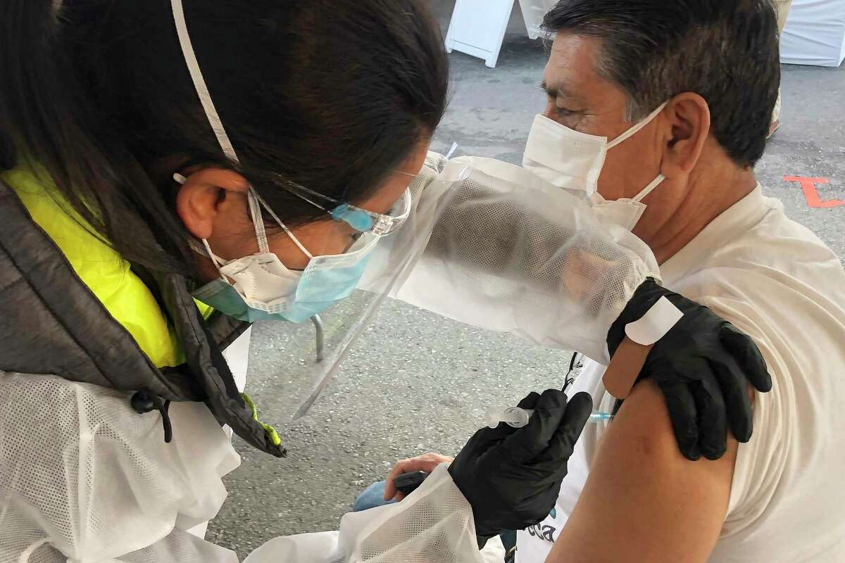 A man receives a coronavirus vaccine shot in the Mission District of San Francisco in February. The number of people newly seeking shots rose in the Bay Area, state and nation this week.