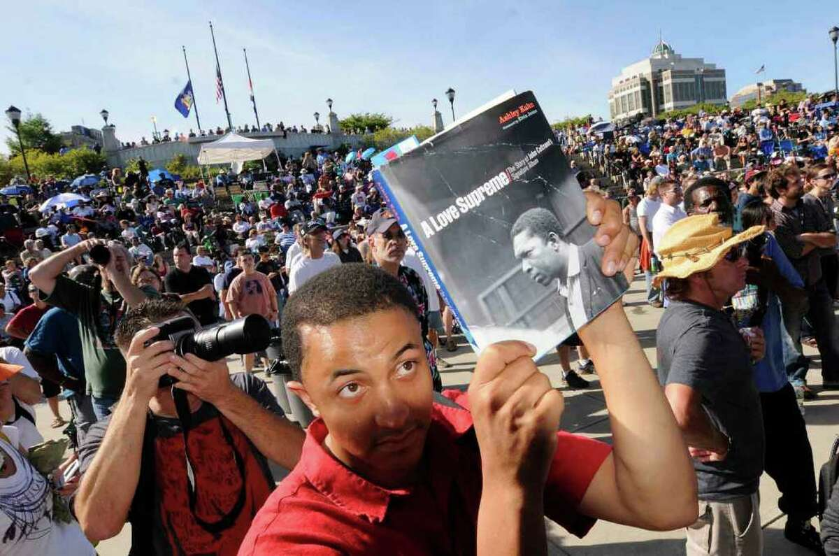 Anthony Lataillade of Mennands holds a book up to Ravi Coltrane about his father jazz legend John Coltrane as Ravi performs with his quartet during the Albany Riverfront Jazz Fest at the Corning Preserve in Albany Saturday afternoon, Sept. 11, 2010. (Michael P. Farrell / Times Union)