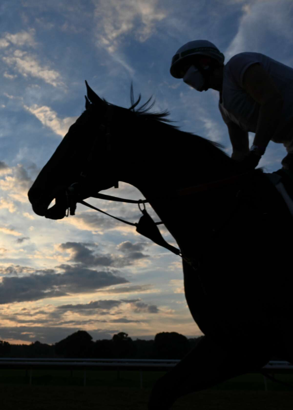 An assistant trainer exercises a thoroughbred around Saratoga Race Course in August, 2020.
