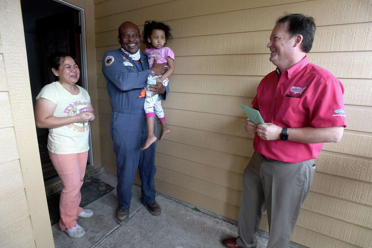 Susie and Henry Ware are suprised by American Air owner Lee Potter and a large group with a brand new Carrier air conditioning system at their home in Port Arthur Thursday. The family have been without air conditioning since their home was destroyed in Harvey and have suffered numerous other tragedies since. They were selected as this year's recipients of American Air's third annual give-away to a family in need. Photo made Thursday, May 13, 2021 Kim Brent/The Enterprise
