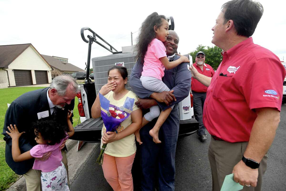 Vernon Pierce picks up Diane Ware as Susie and Henry Ware, holding daughter Valerie, are suprised by American Air owner Lee Potter and a large group with a brand new Carrier air conditioning system at their home in Port Arthur Thursday. The family have been without air conditioning since their home was destroyed in Harvey and have suffered numerous other tragedies since. They were selected as this year's recipients of American Air's third annual give-away to a family in need. Photo made Thursday, May 13, 2021 Kim Brent/The Enterprise
