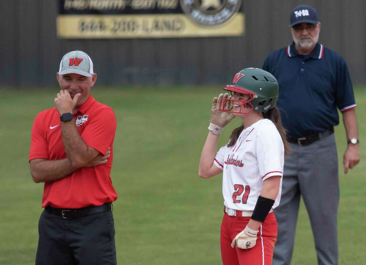 FILE - Haley Mountain #21 of The Woodlands and head coach Tim Borths share a laugh during the first inning of a Region II-6A bi-district playoff game against Dekaney at The Woodlands High School, Thursday, April 29, 2021, in The Woodlands.