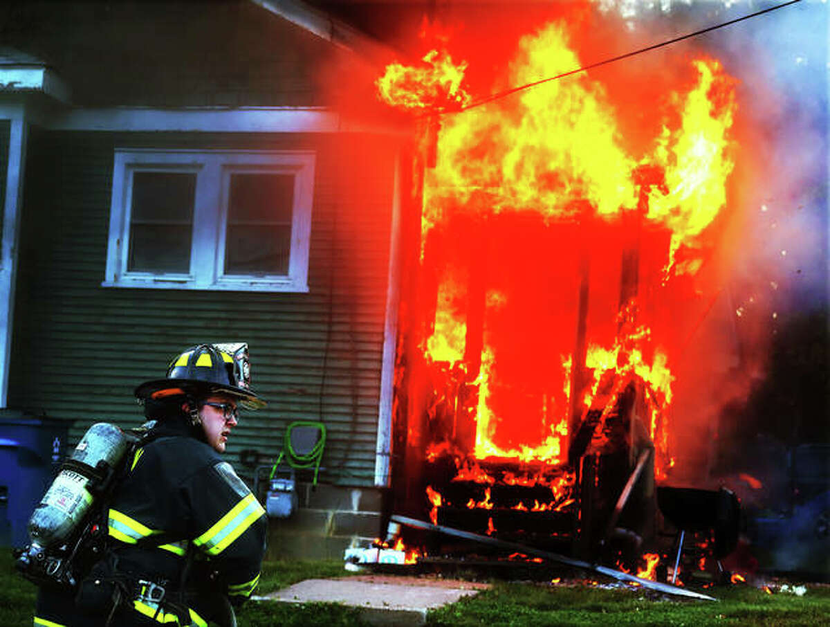 An Alton firefighter waits for water after arriving at a house on the corner of Mayfield and Dorothy avenues about 6:30 p.m. Thursday. The rear of the structure was heavily involved in flames when firefighters arrived. Alton firefighters called for a mutual aid box alarm bringing East Alton firefighters to the scene. The occupant escaped uninjured and no other injuries were reported. The fire was contained mostly to the rear side of the house, but spread into the attic. Firefighters had the fire under control in about 30 minutes, but the home suffered fire and heavy smoke damage.