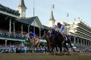 John Velazquez riding Medina Spirit, right, leads Florent Geroux on Mandaloun, Flavien Prat riding Hot Rod Charlie and Luis Saez on Essential Quality to win the 147th running of the Kentucky Derby at Churchill Downs, Saturday, May 1, 2021, in Louisville, Kentucky.