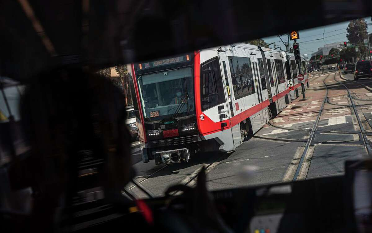A Muni T-Third Street train passes another train going the opposite direction on Third Street in San Francisco.