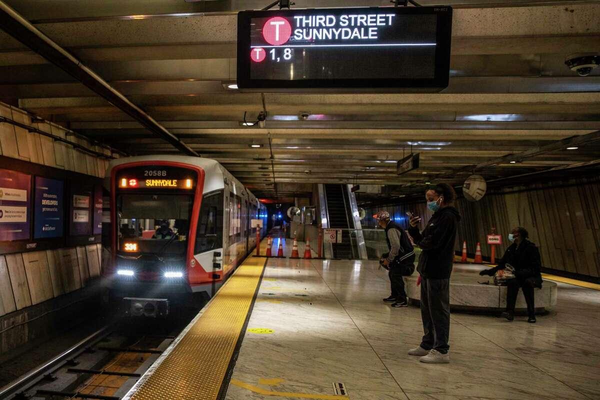 Passengers wait for the Muni T-Third Street train at Embarcadero Station in San Francisco.