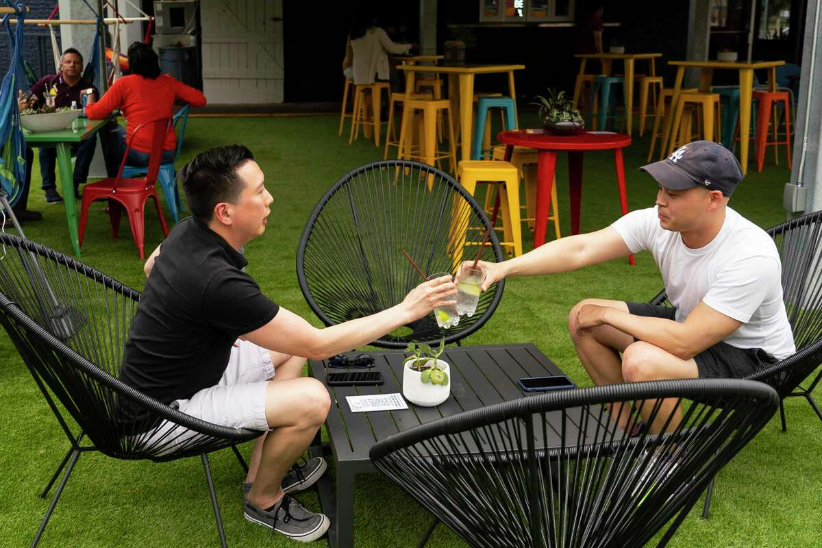 """Son Nguyen, left, and Mikee Hoang toast as they have drinks, Thursday, May 13, 2021, at the bar Space Cowboy in Houston. The CDC relaxed mask guidelines for vaccinated people in an announcement on Thursday. Nguyen and Hoang both work in the health care industry, so they said they have been slowly relaxing their covid precautions as lockdowns ended and things have opened back up. """"We're easing our way into it,"""" said Hoang. """"It's different to try and un-do what we've been doing and getting back to normal."""""""