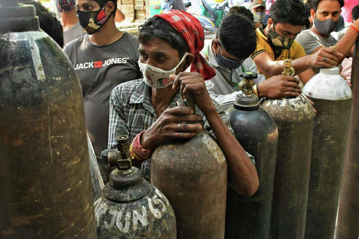 Indians wait to refill oxygen cylinders for COVID-19 patients at a gas supplier facility in New Delhi, India, Saturday, May 8, 2021. Infections have swelled in India since February in a disastrous turn blamed on more contagious variants as well as government decisions to allow massive crowds to gather for religious festivals and political rallies.