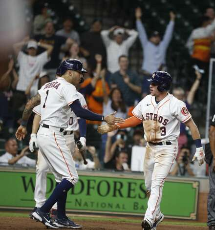 Houston Astros Myles Straw (3) celebrates with Carlos Correa after he scored the winning run on a wild pitch by Texas Rangers pitcher Brett Martin during the eleventh inning of an MLB baseball game at Minute Maid Park, Thursday, May 13, 2021, in Houston. Astros win 4-3. Photo: Karen Warren/Staff Photographer / @2021 Houston Chronicle
