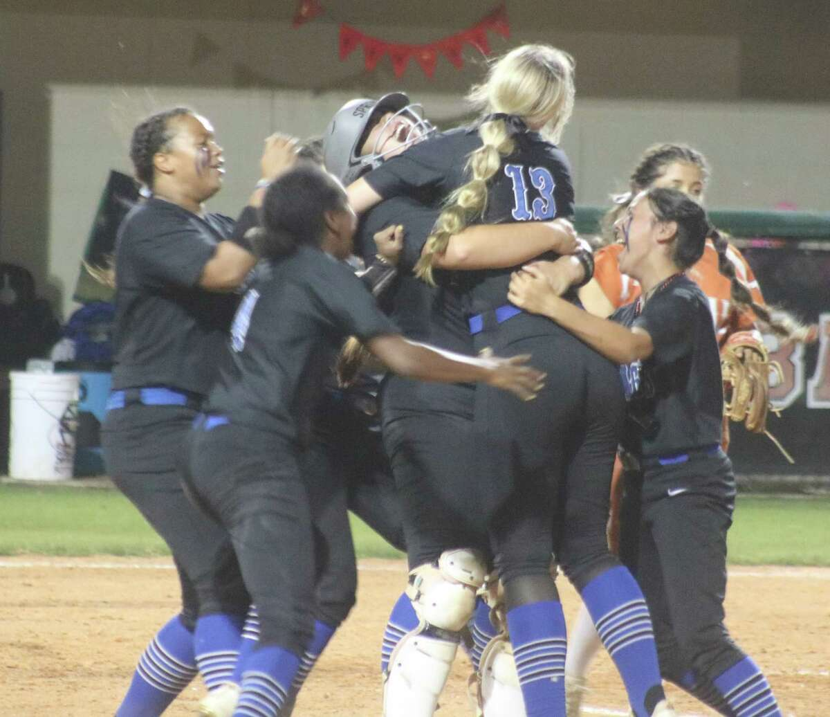 Clear Springs players mob Emma Strood (13), following her walk-off single in the eighth inning Thursday night.