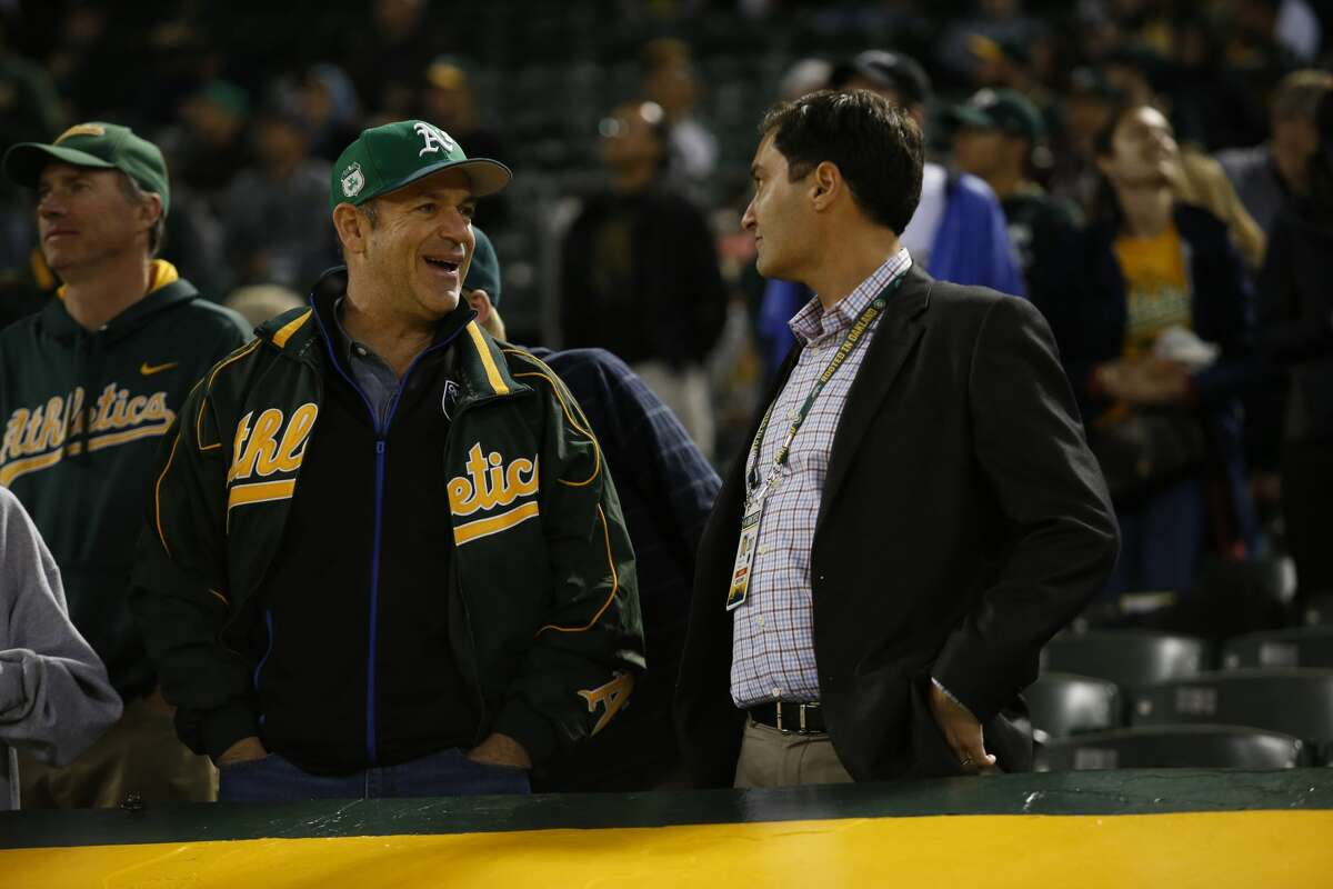 Owner John Fisher and President David Kaval of the Oakland Athletics talk in the stands during a game against the Seattle Mariners on April 21, 2017.