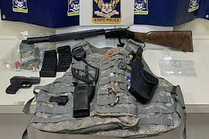 """In the Storrs, Conn., home, police said, investigators seized chemicals and precursors to produce """"energetic materials."""" Police said law enforcement also seized two guns, two high-capacity magazines, rifle ammunition, shotgun ammunition, a ballistic vest, narcotics pills and five marijuana plants in varying stages of growth."""