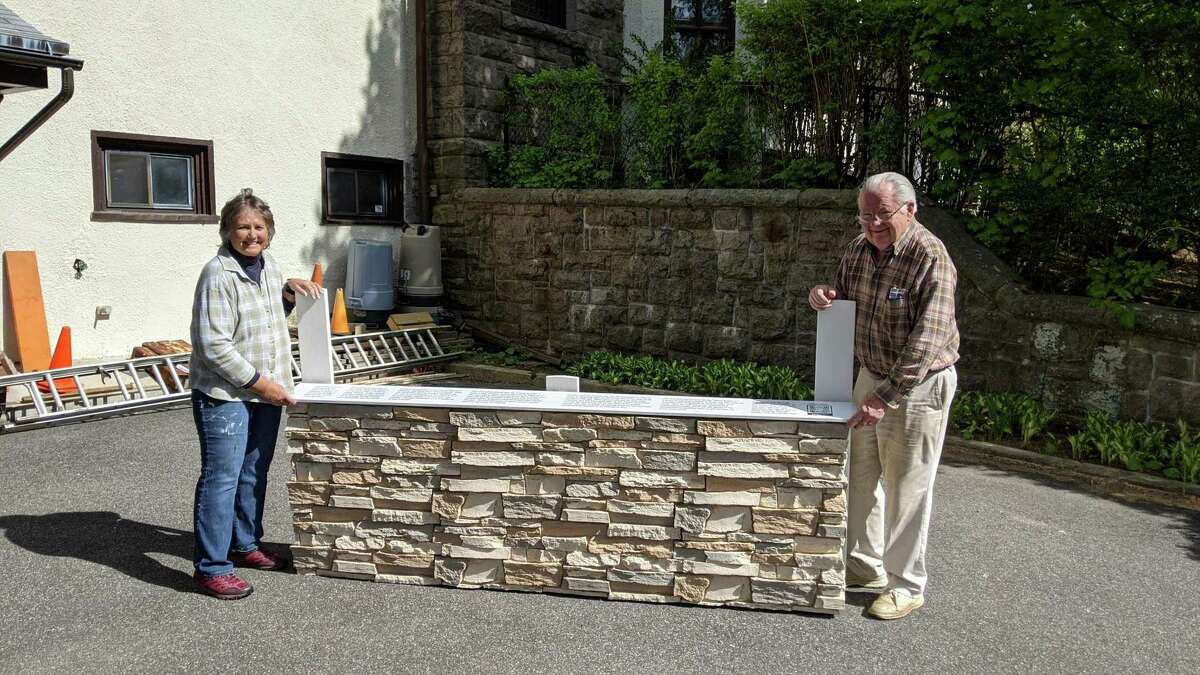 Bonnie Kearns and John Ward pose with the faux-stone base of the Prayer Wall, which was added to mimic the Western Wall in Jerusalem. Visitors wishing to keep their prayers private will be able to share them by writing messages on a piece of paper and concealing them within the cracks of the stones.