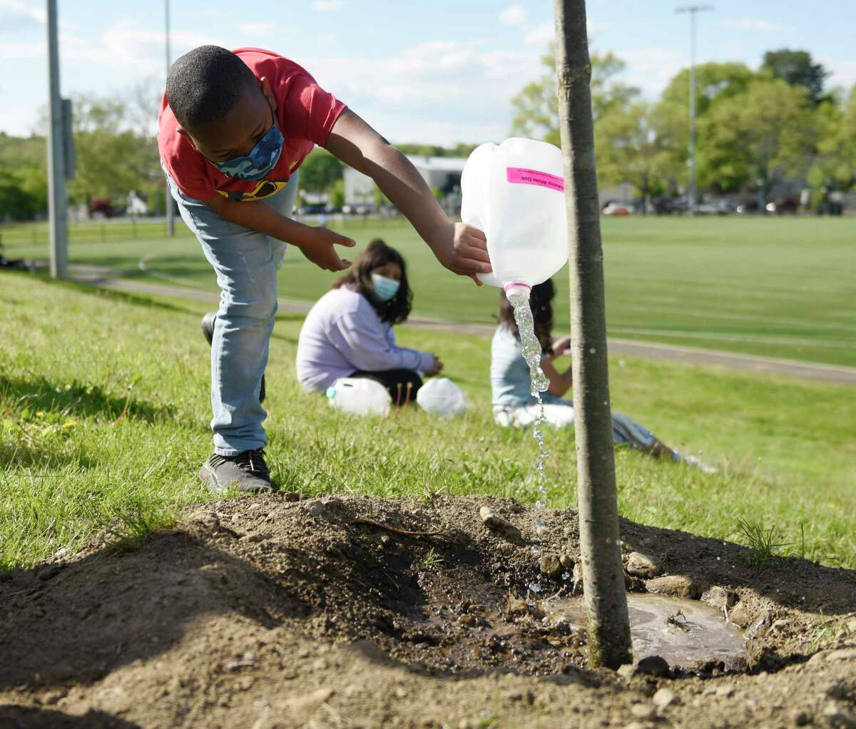Semir B., 10, waters newly-planted Swamp White Oak trees at Lione Park in Stamford, Conn. Thursday, May 13, 2021. Pollinator Pathway Stamford planted 37 new trees in four Stamford parks starting on Earth Day of this year to help create corridors of pollinator-friendly habitat throughout the northeast. With the help of the Boys & Girls Club of Stamford, the new Red Maples and Swamp White Oaks will be watered by Keystone Club and STEM students.