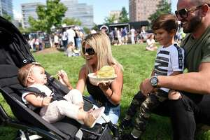 Danbury couple Tatiana and Val Mehmeti eat food from Rice & Beans with their children Luna, 10 months, and London, 5, at the Hey Stamford! Food Festival at Mill River Park in Stamford, Conn. Sunday, Aug. 25, 2019. The two-day event, now in its third year, featured dozens of local food vendors as well as beer, children's games, and live music.