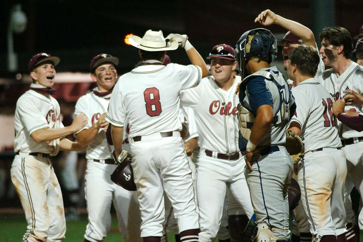 Pearland?•s Caden Ferraro (8) is swarmed by teammates after hitting a home run against Kingwood Thursday, May 13 at Pearland High School.