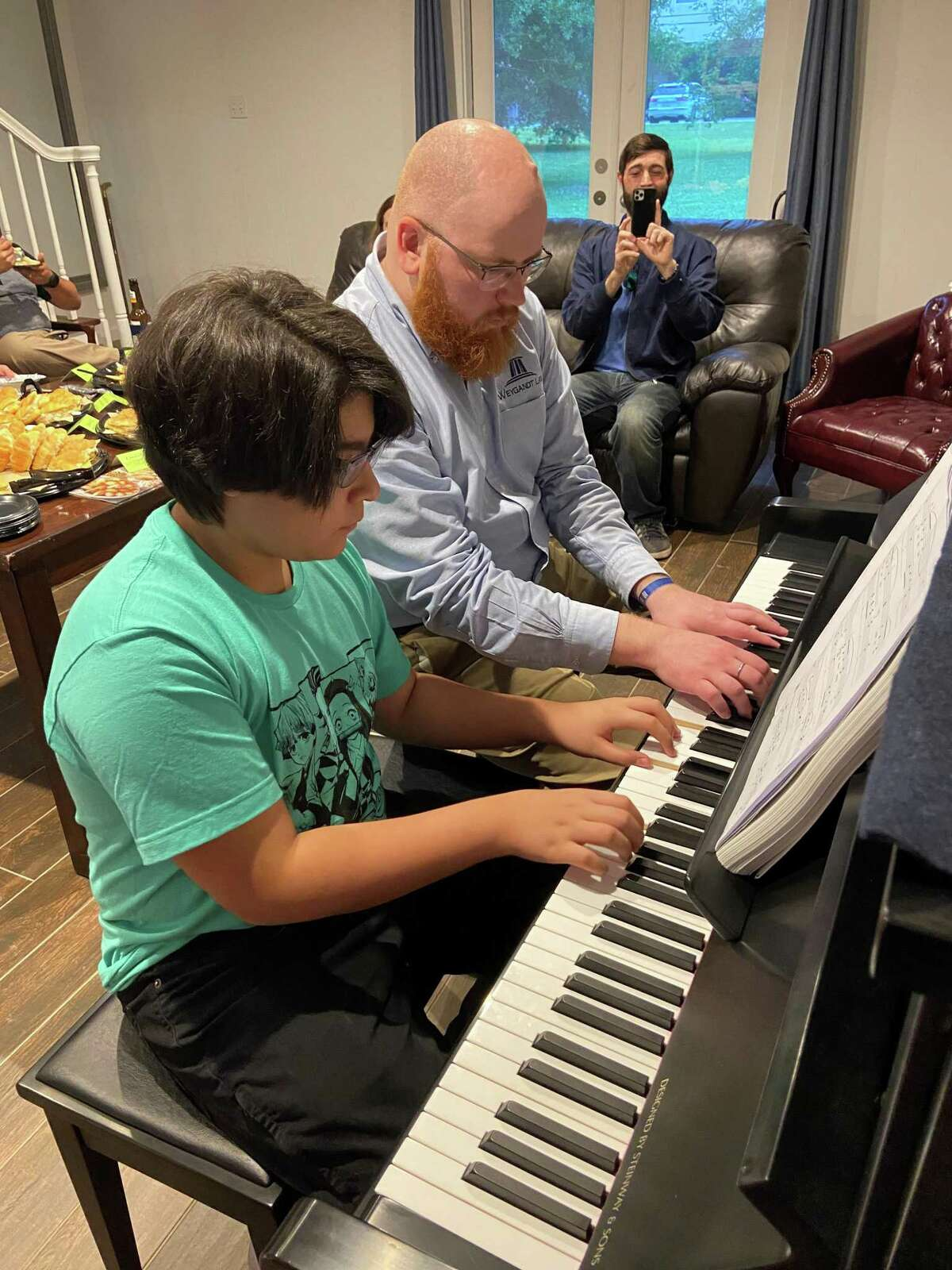 David W. Weygandt of Weygandt Law plays piano with a student showing that not all legal planning has to be a flat experience.