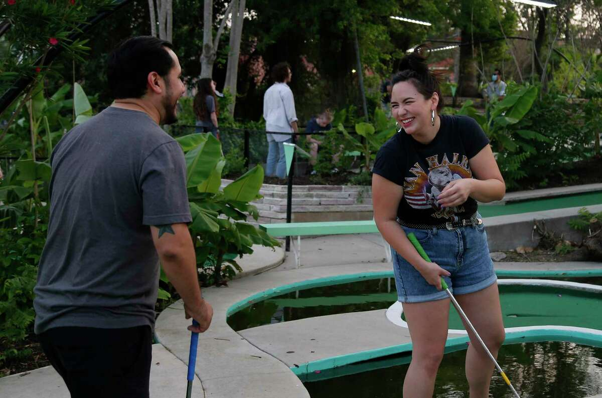 Carly Coburn and Jose DeLeon share a laugh after her ball came back to where she putted during a Sunday round at Cool Crest Miniature Golf.