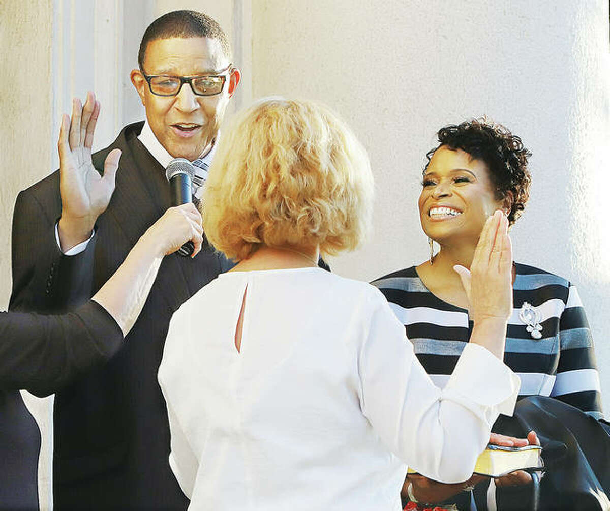 David Goins is sworn in by outgoing Alton City Clerk Mary Boulds, center, with his wife, Sheila, right, at his side Wednesday evening on the steps of Alton City Hall.