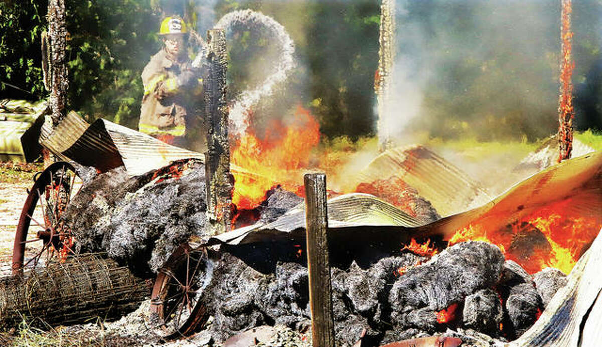 An QEM firefighter sprays water on a shed that burned to the ground Thursday in rural Elsah.