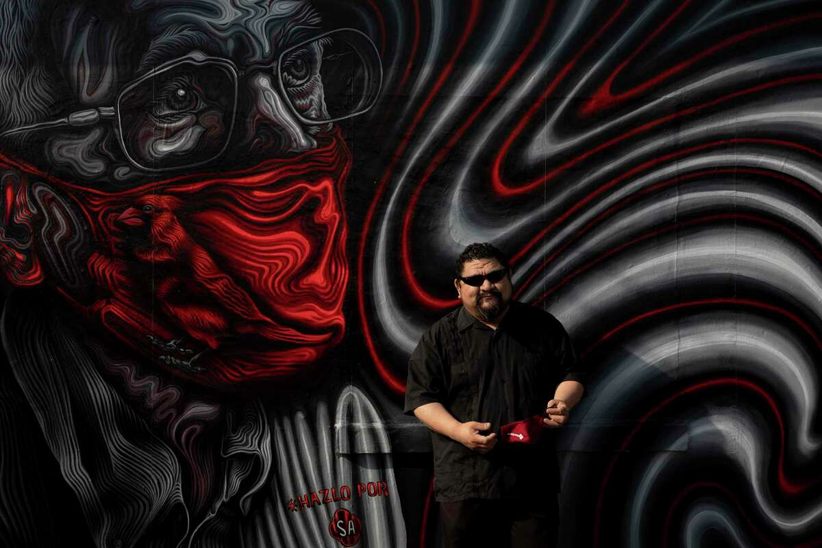 Alex Rubio stands in front of his mural at Express Foods La Norteña Fruit and Grocery - a neighborhood market on the city's West side. This is the first of six murals encouraging people to get their vaccines that will pop up throughout the city.