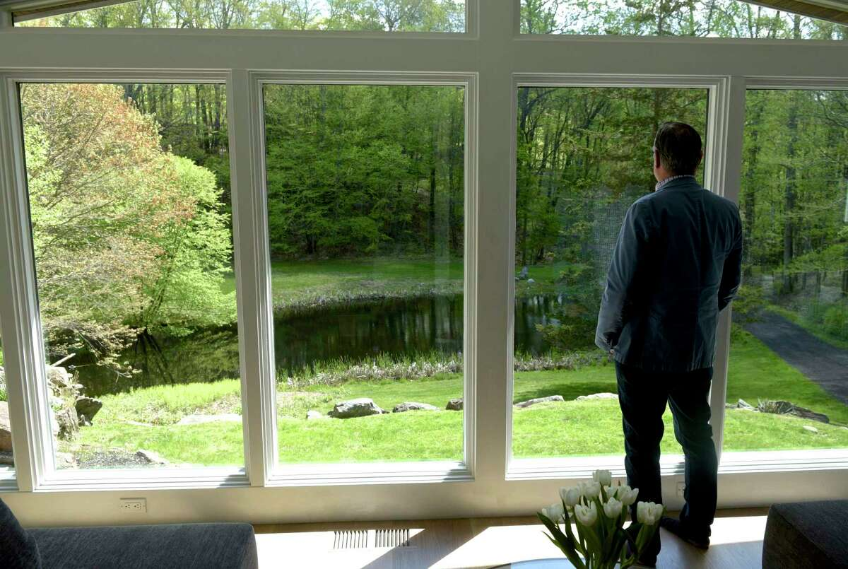 Jeff Phillips, from Madonna & Phillips Real Estate Group at William Pitt Sotheby's International Realty, looks out the window of a new listing from Roxbury, Conn, on Thursday morning, May 13, 2021.