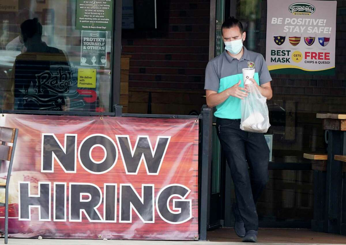 A customer wears a face mask as they carry their order past a now hiring sign at an eatery in Richardson, Texas, Wednesday, Sept. 2, 2020. U.S. companies added jobs at a modest pace last month, a private survey found, a sign that while hiring continues, it is only soaking up a relatively small proportion of the unemployed. (AP Photo/LM Otero)
