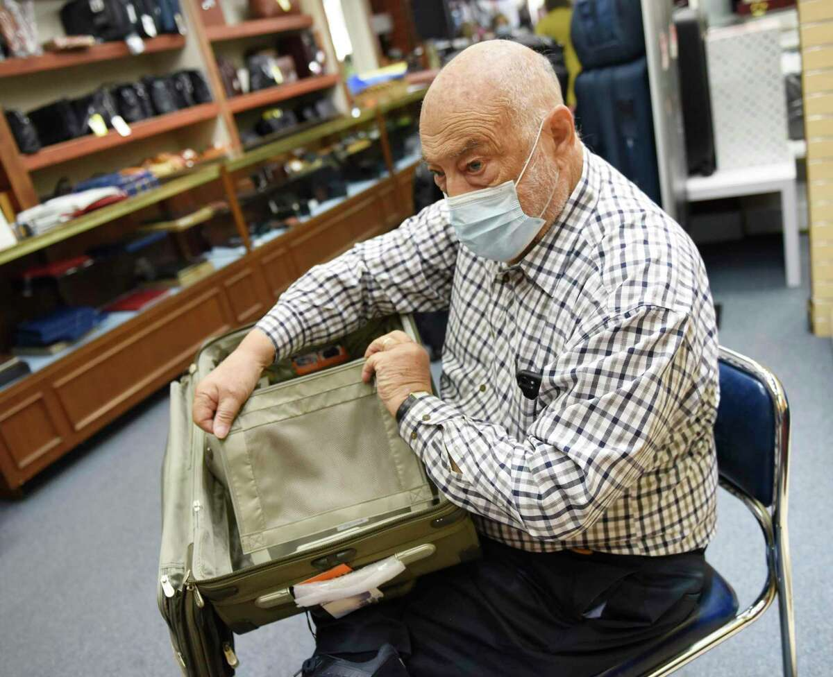 Co-owner Ed Greenberg shows a piece of carry-on luggage inside Wagner's Fine Luggage and Gifts at the High Ridge Shopping Center in Stamford, Conn. Tuesday, May 11, 2021. The longtime mom-and-pop luggage shop will be closing down after more than 150 years in business. The store first opened in Rye, N.Y. in 1853 as a buggy whip and ox collar shop, changing locations and products through the years until it moved to its final location in the High Ridge Shopping Center in 1995.