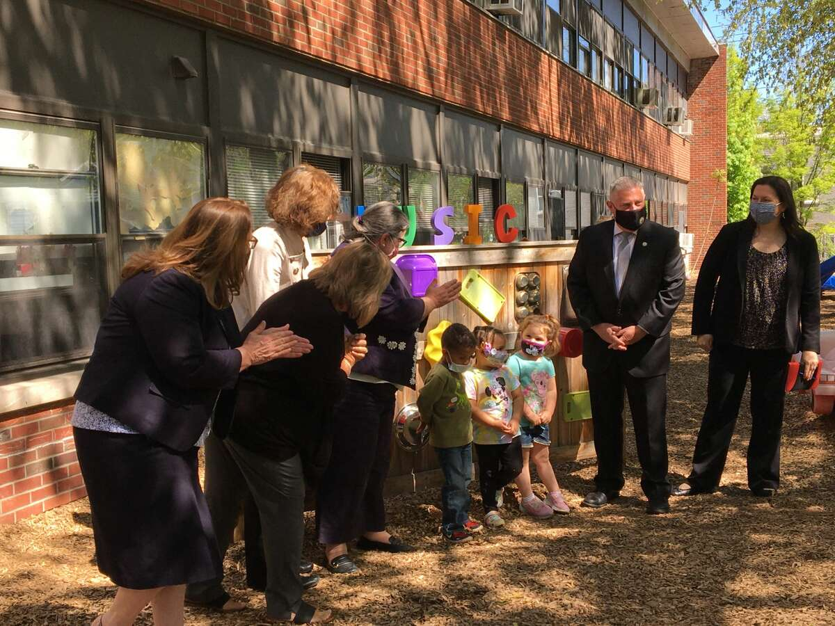 Lawmakers and advocates applaud children in front of a music board at A Child's Place at Unity House in Troy.
