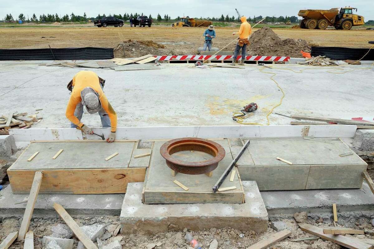 Workers make concrete forms for the drainage system as construction continues in a new subdivision northwest of the Hiway 99 and Bridgeland Creek Parkway, part of the Prairieland Village development Thursday, May. 13, 2021 in Cypress, TX.