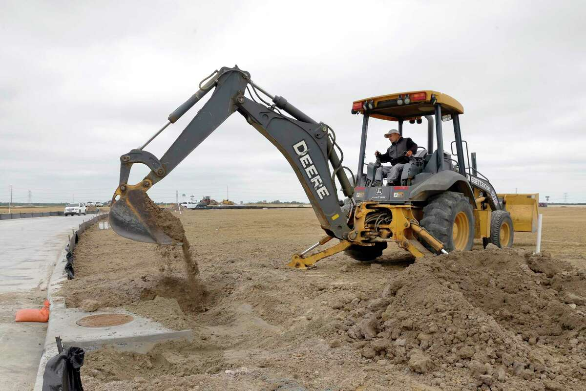 A backhoe moves dirt over a drainage manhole as construction continues in a new subdivision northwest of the Hiway 99 and Bridgeland Creek Parkway, part of the Prairieland Village development Thursday, May. 13, 2021 in Cypress, TX.